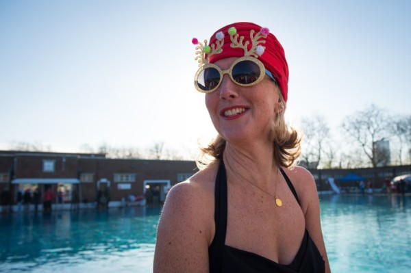 "A woman in novelty sunglasses takes part in the Outdoor Swimming Society's annual ""December Dip"" at Parliament Hill lido in north London on December 13, 2014. AFP PHOTO / LEON NEAL (Photo credit should read LEON NEAL/AFP/Getty Images)"