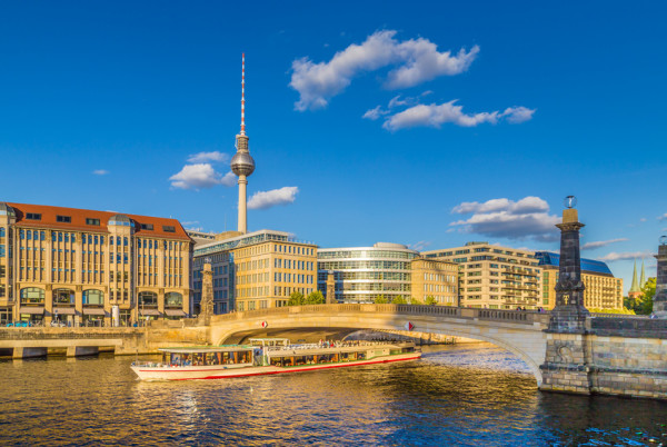 Berlin city center with ship on Spree river at sunset in summer, Germany